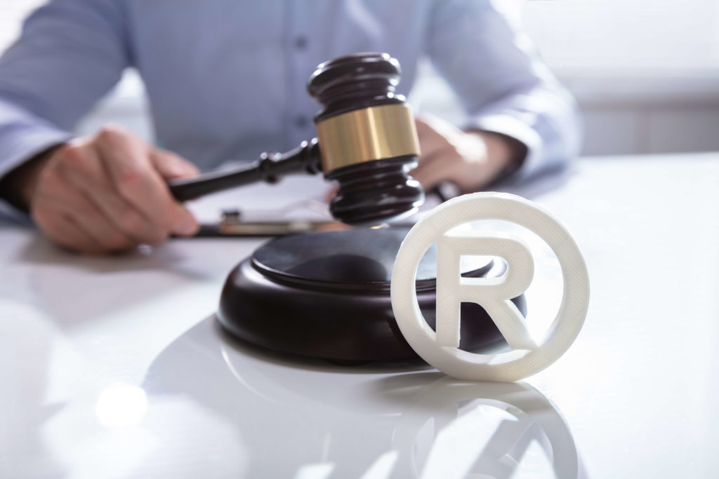 registered trademark symbol on desk with gavel in the background